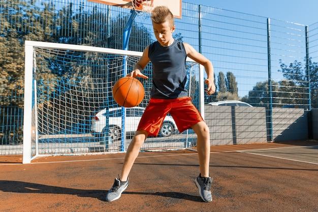 ボールを持つ白人の10代の少年ストリートバスケットボール選手