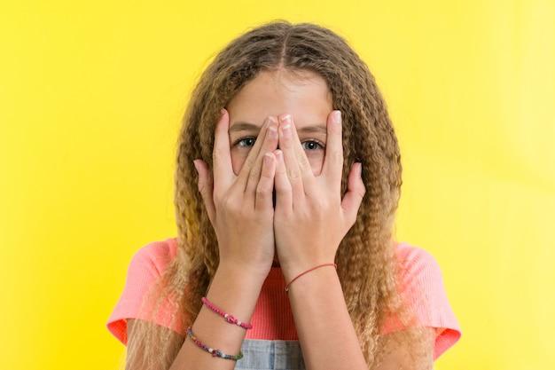 10代の少女の肖像画は指の間から覗く