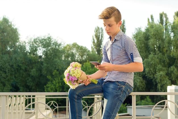花の花束と10代の少年の屋外のポートレート。
