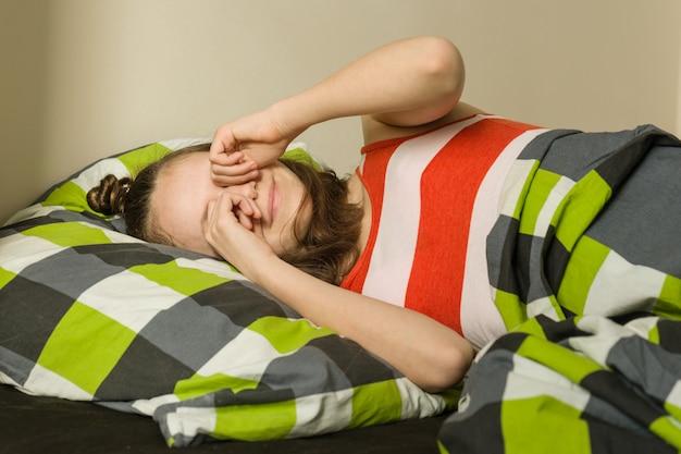 トップビューのベッドで枕に横になっている10代の少女