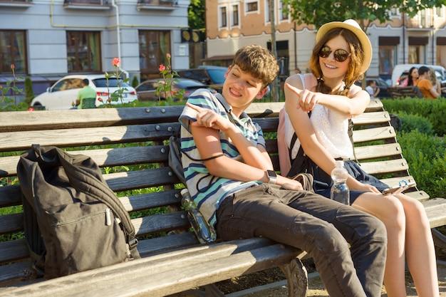 10代の友人の女の子と男の子の街のベンチに座って