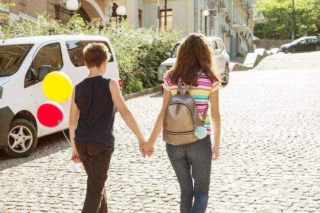 手を繋いでいる10代の若者の背面図。友情の初恋