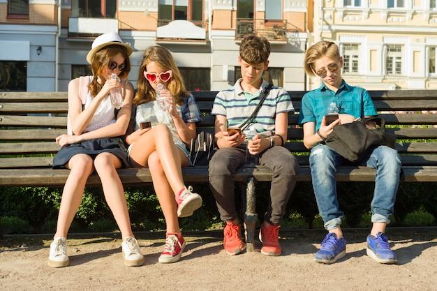 10代の友達の女の子と男の子のベンチに座って