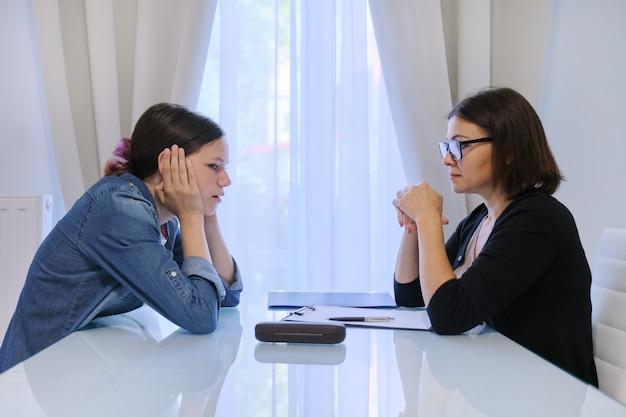 彼女の気持ちについてカウンセラー心理学者と話している10代の少女