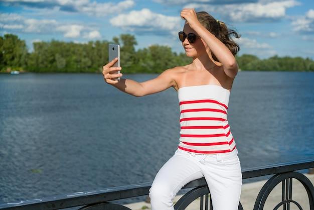 10代の少女がスマートフォンでビデオを撮影