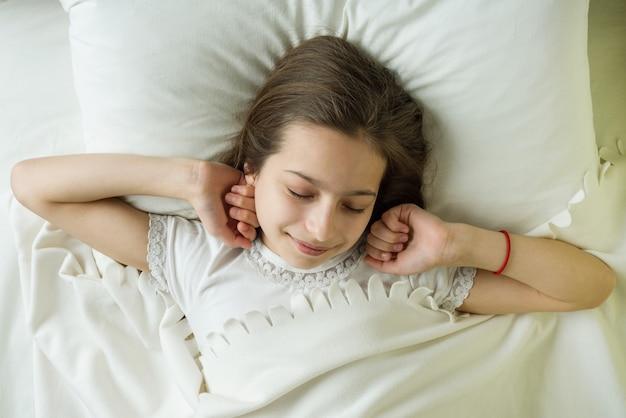 10代の少女が目を覚ます、枕の上に横たわる笑顔