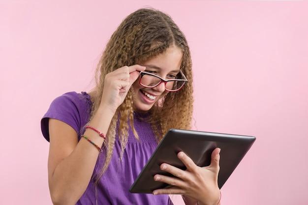 デジタルタブレットを使用してメガネと10代の学校の女の子