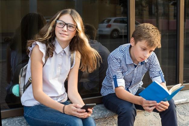 本を読んで、スマートフォンを使用している10代の若者。
