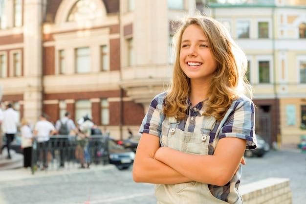 組んだ腕を持つ10代の女の子の屋外のポートレート