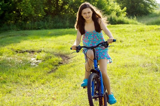 芝生の上の10代の少女乗馬自転車