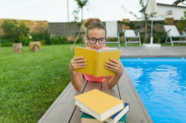 メガネの10代の少女は本を読みます