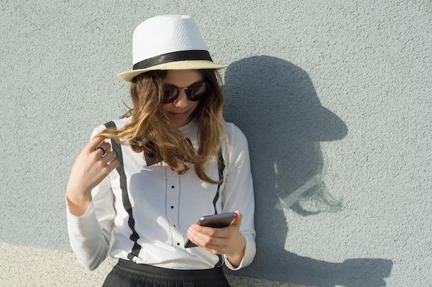 帽子の10代の少女の屋外のポートレート