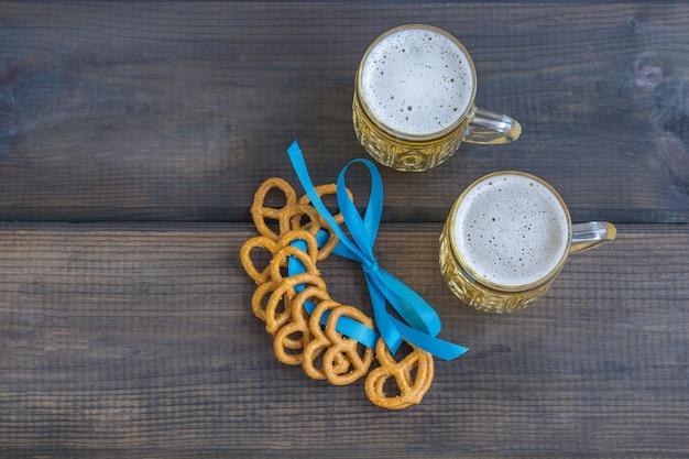 10月祭のコンセプト。暗い木製のテーブルの上の塩のプリッツェル、ブレッツェル、青いテープの軽食とビールジョッキ。