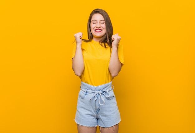 幸せと成功を感じて、拳を上げる黄色のシャツを着ている若い女性10代。勝利のコンセプト。