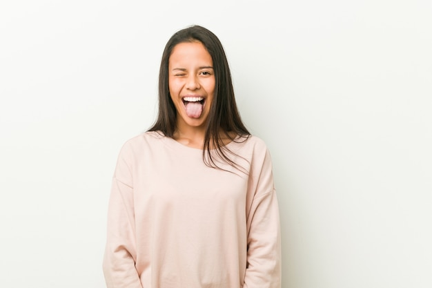 若いかわいいヒスパニック系10代女性面白いとフレンドリーな舌を突き出しています。