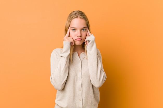 キュートで自然な10代の女性は、人差し指を頭に向けたまま、タスクに集中しました。