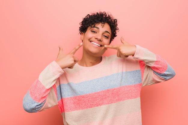 若い混合アフリカ系アメリカ人の10代女性の笑顔、口に指を指しています。