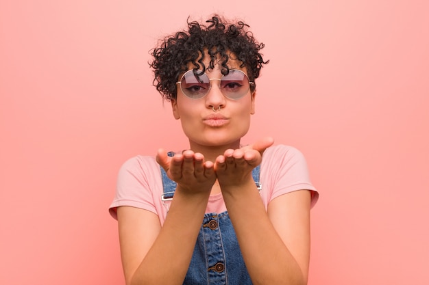 若い混合アフリカ系アメリカ人の10代女性の唇を折りたたみ、手のひらを保持して空気キスを送信します。