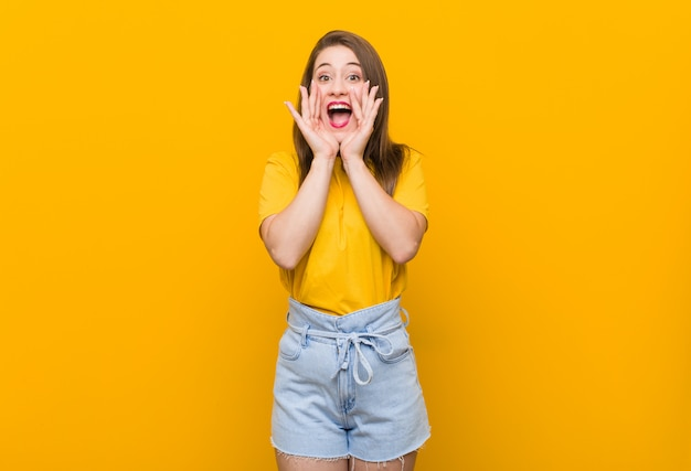叫んでいる黄色のシャツを着た若い女性10代は前に興奮しています。