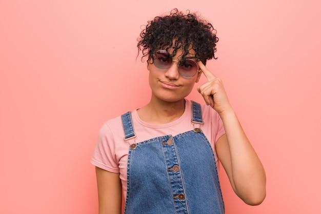 若い混合アフリカ系アメリカ人の10代女性の指で寺院を指して、考えて、タスクに焦点を当てた。