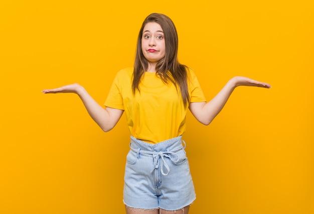 ジェスチャーを疑って肩を疑い、肩をすくめて黄色のシャツを着た若い女性10代。