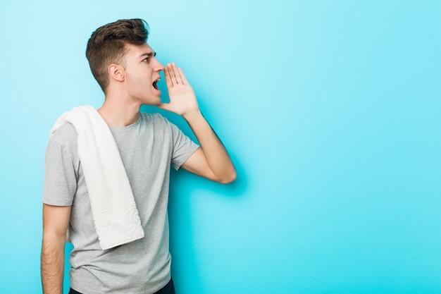 若いフィットネス10代の男が叫んで、開いた口の近くの手のひらを保持しています。