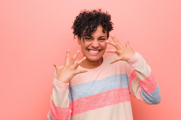 若い混合アフリカ系アメリカ人の10代女性が緊張した手で叫んで怒っています。