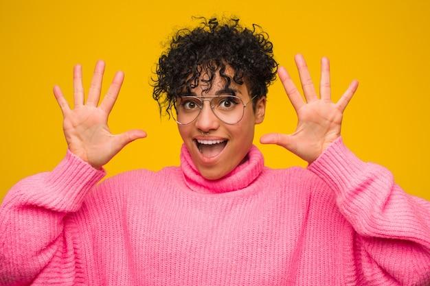 Молодая афро-американская женщина нося розовый показ свитера 10 с руками.