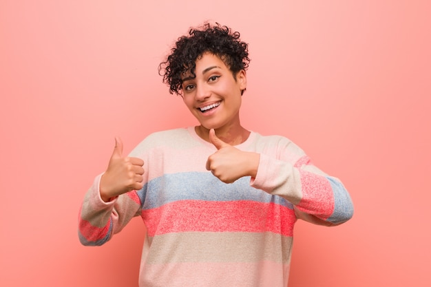 若い混合アフリカ系アメリカ人の10代女性の両方の親指を上げて、笑顔と自信を持って。