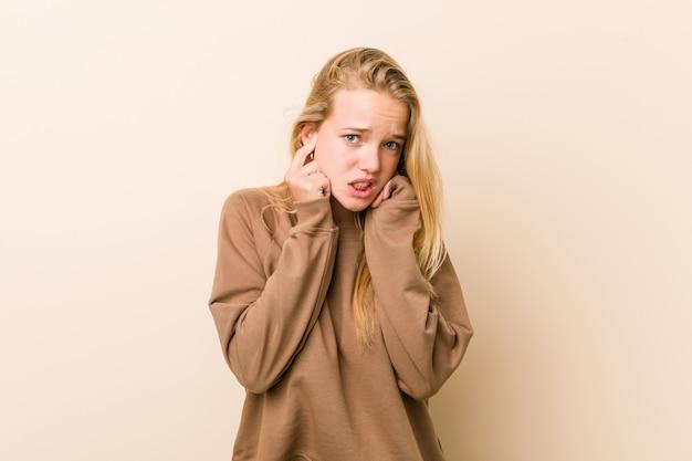 キュートで自然な10代女性の手で耳を覆っています。
