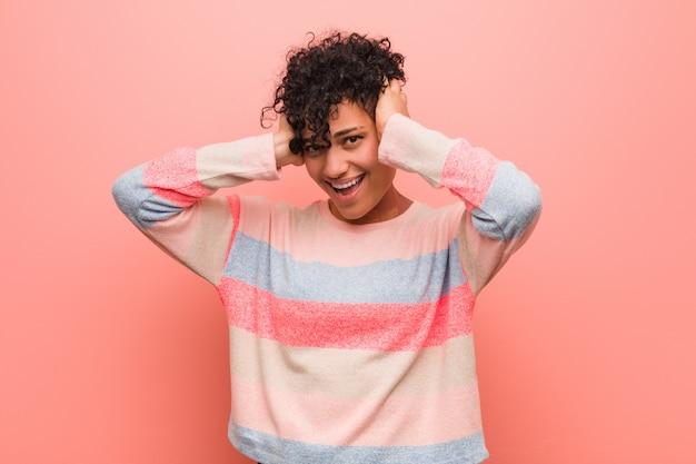 若い混合アフリカ系アメリカ人の10代女性は、手を頭の上に保持して喜んで笑います。幸福の概念。
