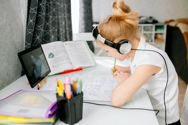 十代の少女の学校の生徒は、自宅からリモートの家庭教師とオンラインで勉強するヘッドフォン会議通話を着ています。ラップトップを使用して10代の学生が遠隔教師とウェブカメラビデオチャット学習レッスンで話しています。