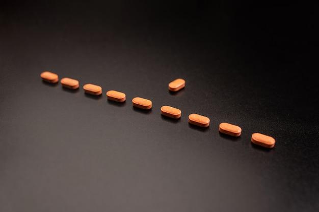 10個のオレンジ色の錠剤。健康の概念。薬理学の概念。