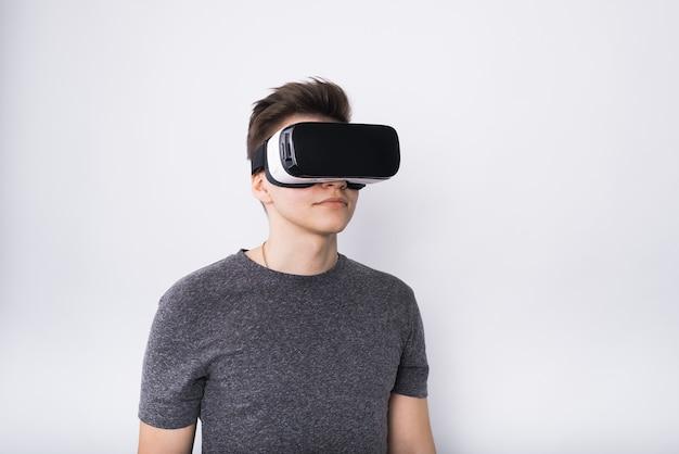 バイアグラスの若い男。 10代の若者が仮想現実の眼鏡で遊ぶ