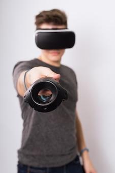 若い男がバイアゲームのコントローラーを持っています。 10代の若者が仮想現実の眼鏡で遊び、ジョイスティックとゲームパッドを検討する