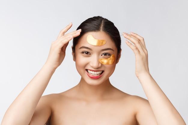 アジアの美しさの10代の女性は目の下の金のアイマスクパッチで彼女の肌をケアします。