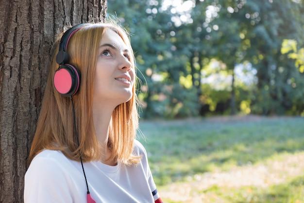 屋外の木にもたれて大きなピンクのイヤホンで音楽を聴く赤い髪の10代の少女の肖像画。