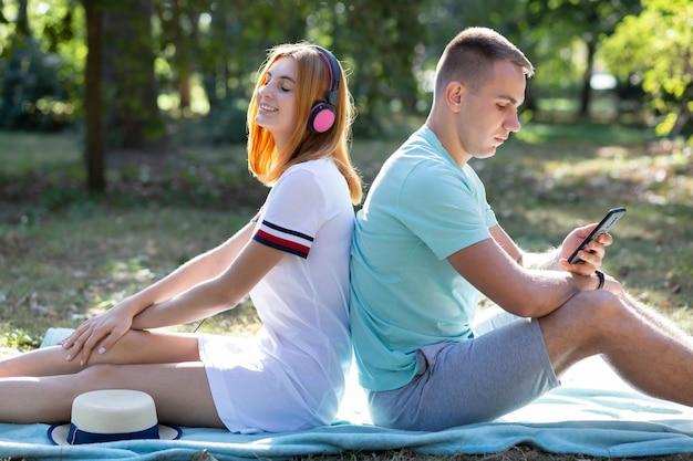 夏の公園で屋外楽しんで若い10代のカップル。ピンクのイヤホンで音楽を聴く赤い髪の少女と販売電話でチャットの少年。