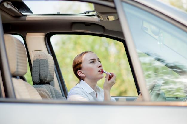 危険運転のコンセプト。車を運転しながら適用を行う彼女の唇を描く若い女性ドライバー赤髪の10代の少女