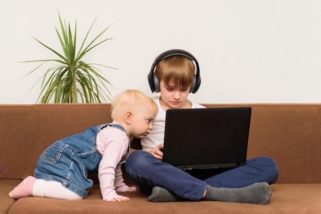ノートパソコンと女の赤ちゃんが付いているソファーに座っている10代の少年が不思議なことにモニターを見てください。ジェネレーションアルファのコンセプト