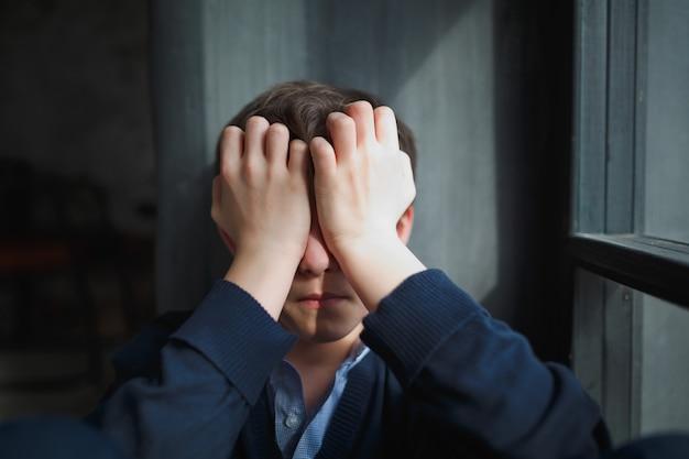 物思いにふける悲しい10代の少年は窓に座って、彼の手で顔を閉じます