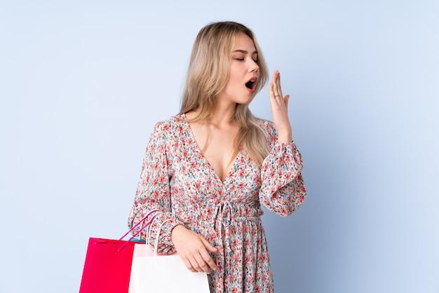 あくびと手で大きく開いた口を覆っている青い壁に買い物袋を持つ10代のロシアの女の子