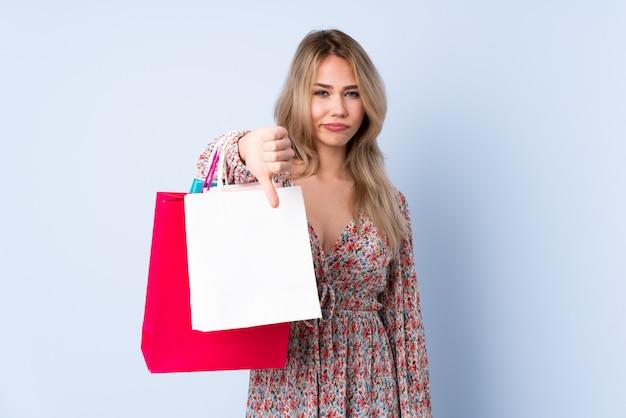 否定的な表現でダウン親指を示す青い壁に買い物袋を持つ10代のロシアの女の子