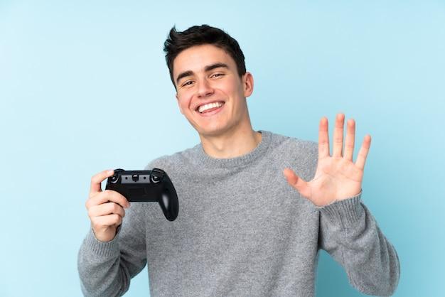 幸せな表情で手で敬礼青い壁にビデオゲームコントローラーで遊んで10代の白人男性
