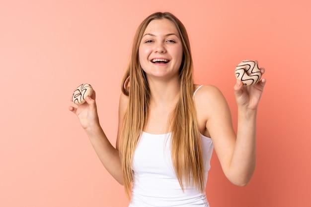 幸せな表情でドーナツを保持しているピンクのスペースに分離された10代のウクライナの女性
