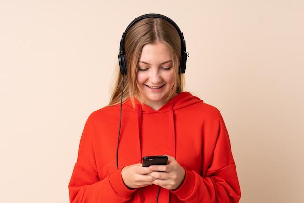 音楽を聴くと携帯を探しているベージュに分離された10代のウクライナの女の子
