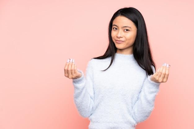 ピンクに分離された10代の中国人女性
