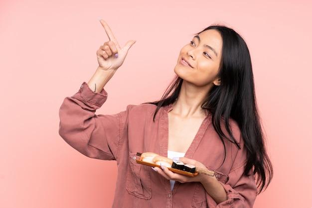 ピンクに分離された寿司を食べる10代のアジアの女の子