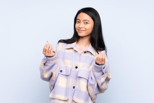 お金のジェスチャーを作る青い壁に10代の中国人女性