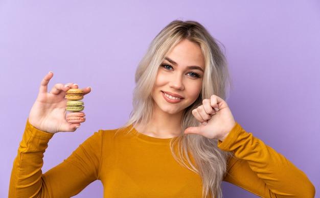 カラフルなフランスのマカロンを保持し、誇りに思っている分離の紫色の壁を越えて10代の女性